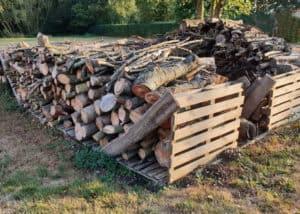 Bei der Brennholzlagerung im Innen- wie Außenbereich ist es besonders wichtig, zwischen Boden und Wänden genug Platz für Luftzirkulation zu lassen.